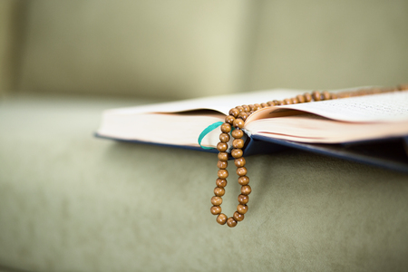 man praying: The Koran with rosary beads