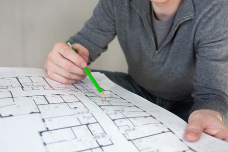 builder: A construction worker on a construction site check documents with pencil in his hand