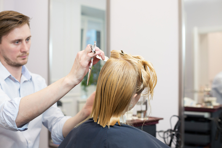 Handsome hairdresser making highlighting coloring and haircut of blonde female client in hairdressing salon