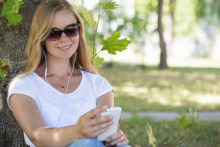 net surfing: A beautiful blonde woman sitting in a park and surfing in the net with her smartphone