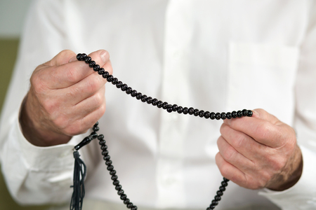 religious clothing: Praying hands of an old man holding rosary beads. Selective focus Stock Photo