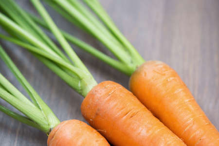 carrot: Raw carrots with green tops on wooden background Stock Photo