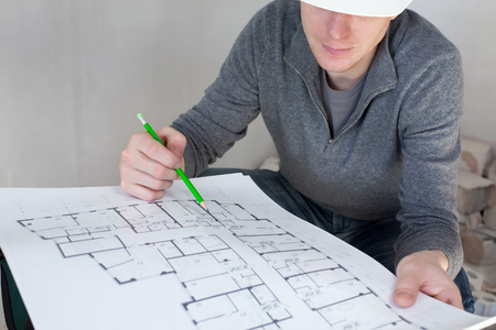 a check: A construction worker on a construction site check documents with pencil in his hand