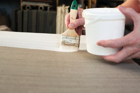 priming: An artist priming canvas for oil painting. Selective focus