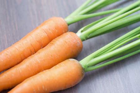 zanahoria: Las zanahorias crudas con hojas verdes sobre fondo de madera Foto de archivo