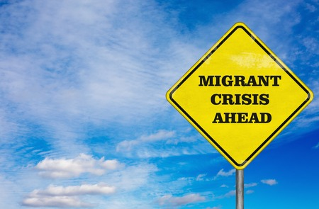 migrant: A road sign Migrant Crisis on a sky background