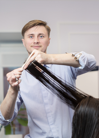 haircut: A handsome hairdresser making a haircut for a brunette girl Stock Photo