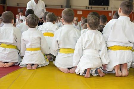 judo: Niños en kimono sentado en tatami en seminario de artes marciales. Enfoque selectivo