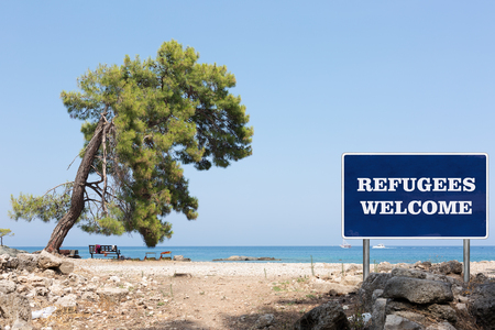 shore: The road sign with Refugees welcome sign on a background with sea shore Stock Photo