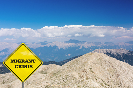migrant: The road sign with Migrant crisis sign on a background with mountains