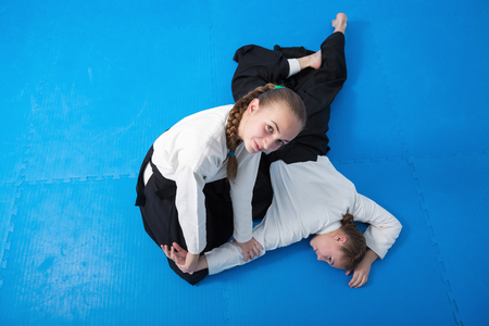 aikido: Two girls in black hakama practice Aikido on martial arts training Stock Photo