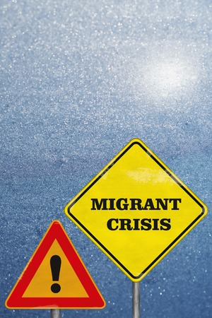 vertical orientation: A road signs Attention and Migrant Crisis on blue winter background. Vertical orientation
