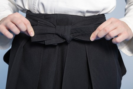 sensei: Hands of a girl tie a bow-knot on hakama for martial arts training