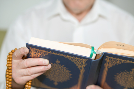 An old man hand with rosary beads  holding the Koran. Selective focus