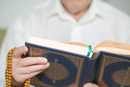 Une main vieille homme avec un chapelet tenant le Coran. mise au point sélective