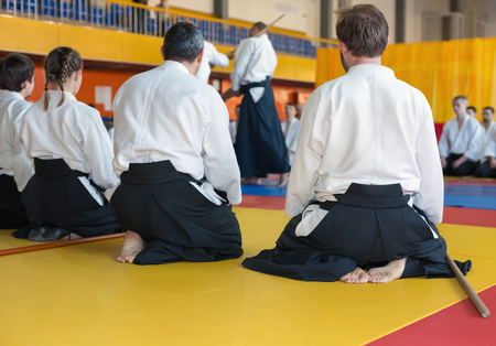 People in kimono and hakama sitting on tatami on martial arts training. Selective focus