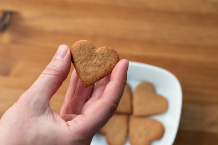 A females hand holding heart-shaped cookie Stok Fotoğraf