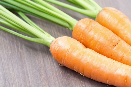 Raw carrots with green tops on wooden background Stockfoto