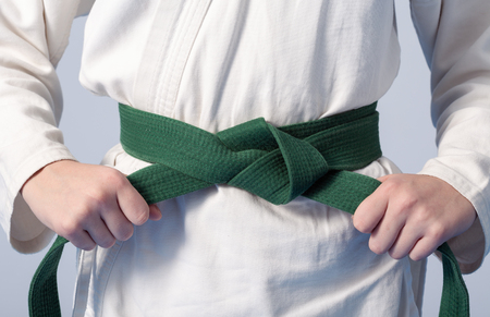 Hands tightening green belt on a teenage dressed in kimono for martial arts