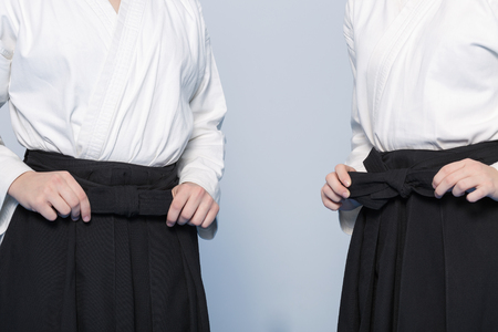 sensei: Girls hands tie a bow-knot on hakama for martial arts training Stock Photo