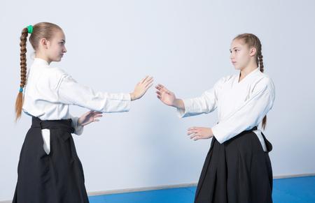 Two girls in black hakama practice Aikido on martial arts training on blue tatami Foto de archivo