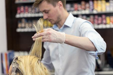 bleaching: A  blonde female bleaching hair in studio. Selective focus