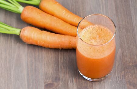 carrot: Healthy carrot juice in a glass and raw carrots on a wooden background. Shallow dof