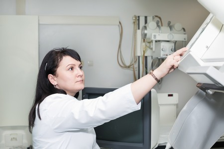 x ray equipment: Brunette female doctor working with an x-ray machine