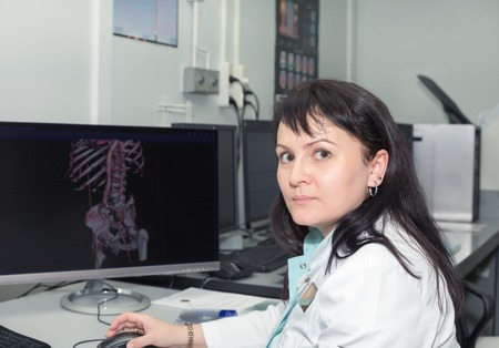 ct: Brunette female doctor examining an CT scanner results