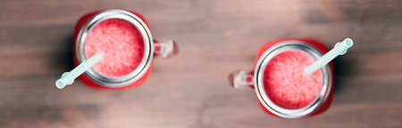 horozontal: A flat shallow dof view of two watermelon smoothies in a mason jars with tubes on wooden background. Selective focus on tubes