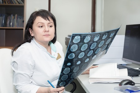 x ray equipment: Brunette female doctor examining an CT scanner results