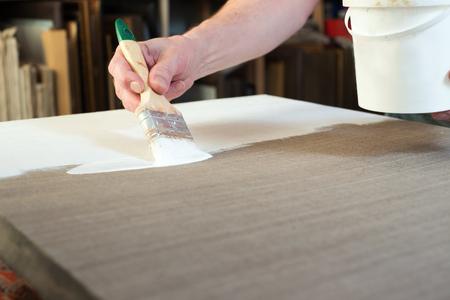 priming: An artist priming canvas. Selective focus