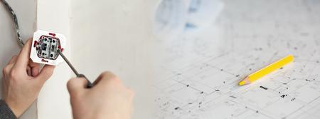 Un Manos de electricista con destornillador Instalación del zócalo de pared con planos en un fondo