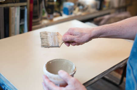 priming brush: An artist priming canvas. Selective focus