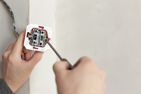 wall socket: Close-up Of Electrician Hands With Screwdriver Installing a Wall Socket