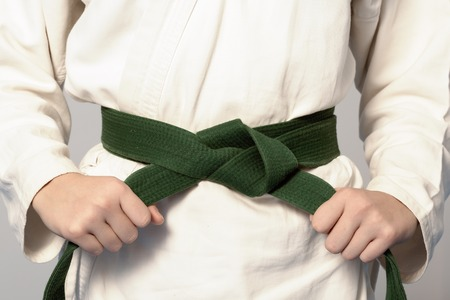 Hands tightening green belt on a teenage dressed in kimono for martial arts. Sepia toning