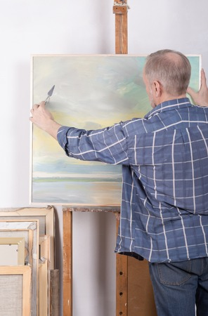 palette knife: An artist painting with a palette knife in his studio Stock Photo