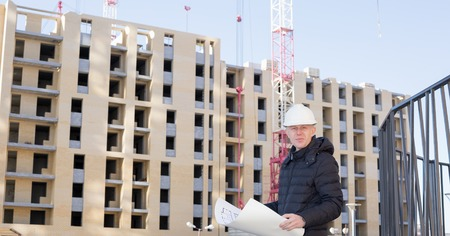 unsatisfied: An unsatisfied engineer on a construction site with cranes and blueprints in hands