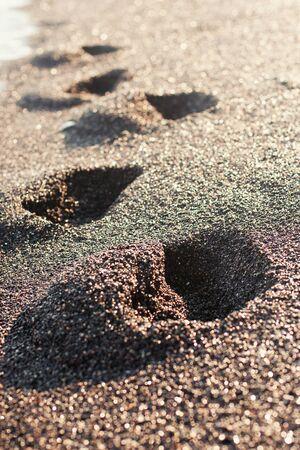 footsteps: Footsteps on the black volcanic sand