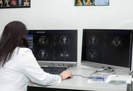 x ray equipment: A back view of a brunette female doctor examining CT scanner results