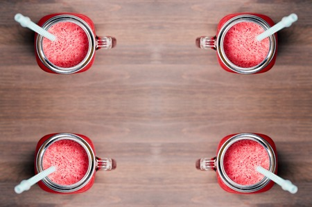 horozontal: A top shallow dof view of four watermelon smoothies in a mason jars with tubes on wooden background