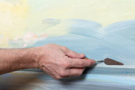 An artists hand painting with a palette knife in studio Stock Photo