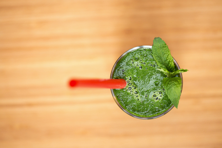 red tube: A green smoothie in a glass with red tube and mint leaves on wooden background. Shallow dof