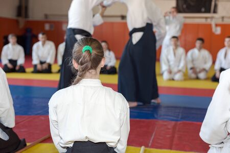 sensei: A girl in hakama sitting on tatami on martial arts training with other people. Selective focus