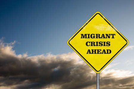 undesirable: A road sign Migrant Crisis Ahead on a dramatic sky background