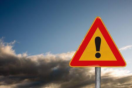 point exclamation: Attention, signe de la route avec un point d'exclamation sur un fond avec un ciel dramatique