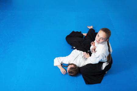 sensei: Two girls in black hakama practice Aikido on martial arts training on blue tatami Stock Photo
