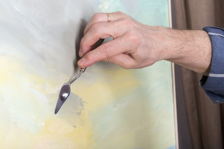 palette knife: An artists hand painting with a palette knife in studio Stock Photo