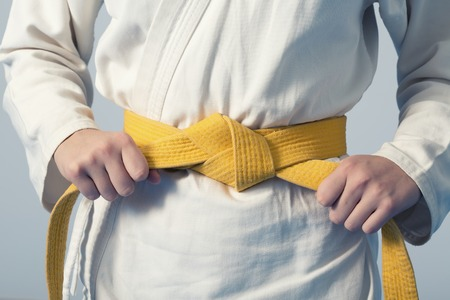 sensei: Hands tightening yellow belt on a teenage dressed in kimono for martial arts