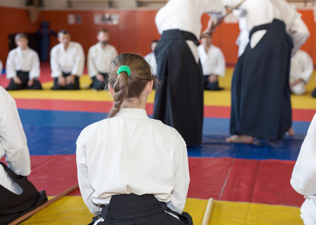A girl in kimono and hakama sitting on tatami on martial arts seminar. Selective focus Foto de archivo
